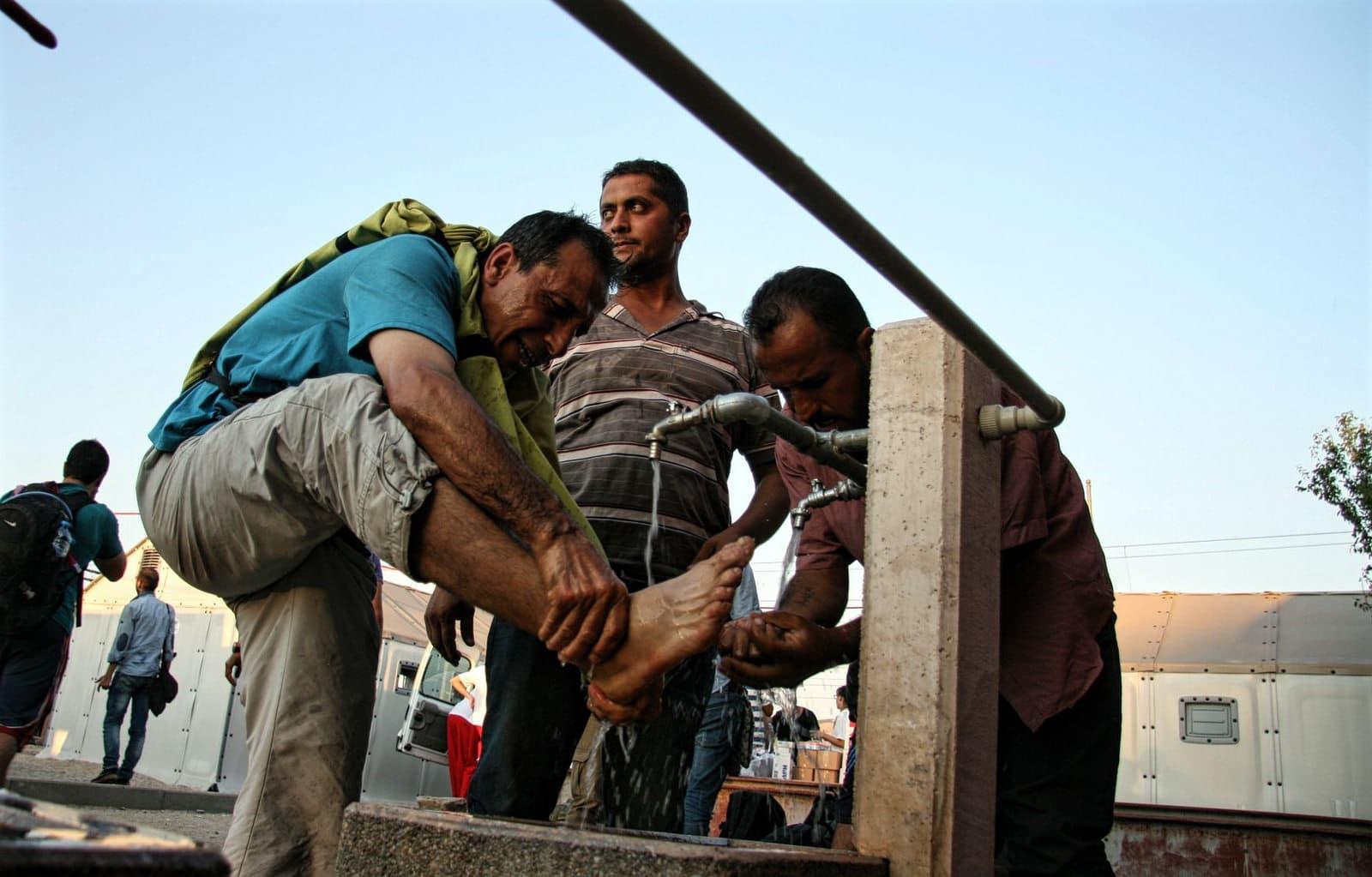 Macedonia, 3 settembre 2015. Migranti si lavano i piedi prima di attraversare il confine con la Serbia. Foto di IFRC su Flickr, licenza CC.