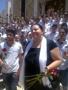 Marcell Shehwaro al funerale di sua madre, assassinata dalle forze del regime siriano a un checkpoint nel giugno 2012. I compagni attivisti rendono tributo portando delle rose rosse. Immagine concessa da Marcell Shehwaro.