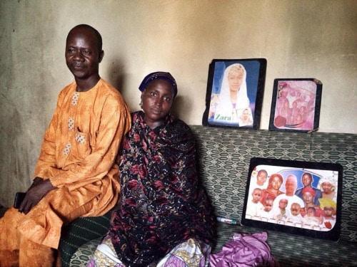 Sani e sua moglie Zara posano davanti a un ritratto di famiglia, foto di Glenna Gordon dalla piattaforma Everyday Africa.