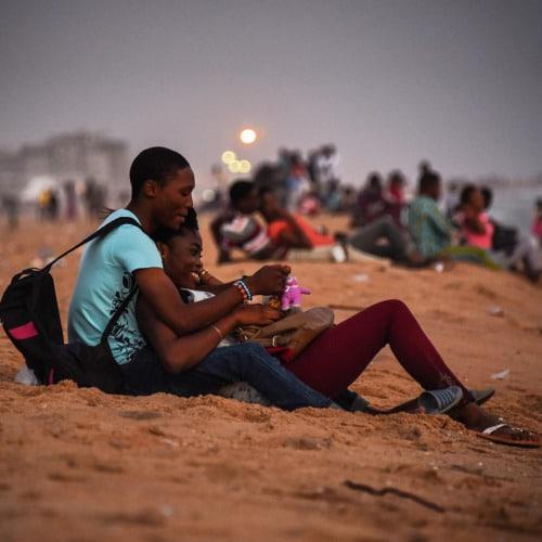 Una coppia guarda il tramonto su una spiaggia di Cotonou, Benin. Foto di Ricci Shryock sulla piattaforma Everyday Africa.