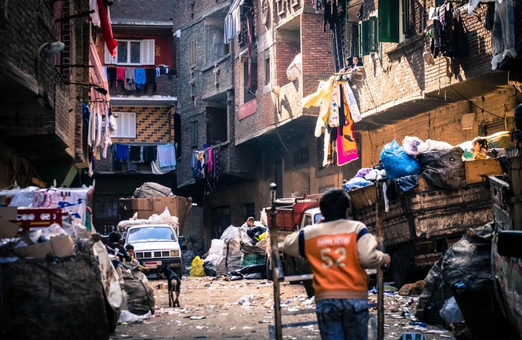 In uno dei vicoli di Muqattam un bambino 'zabbaleen' spinge uno dei tantissimi carrelli che serve a trasportare la spazzatura, sulla sua destra un bambina infilata nel retro di un camion fa una prima selezione dei rifiuti. Foto di Angelo Calianno su licenza CC.