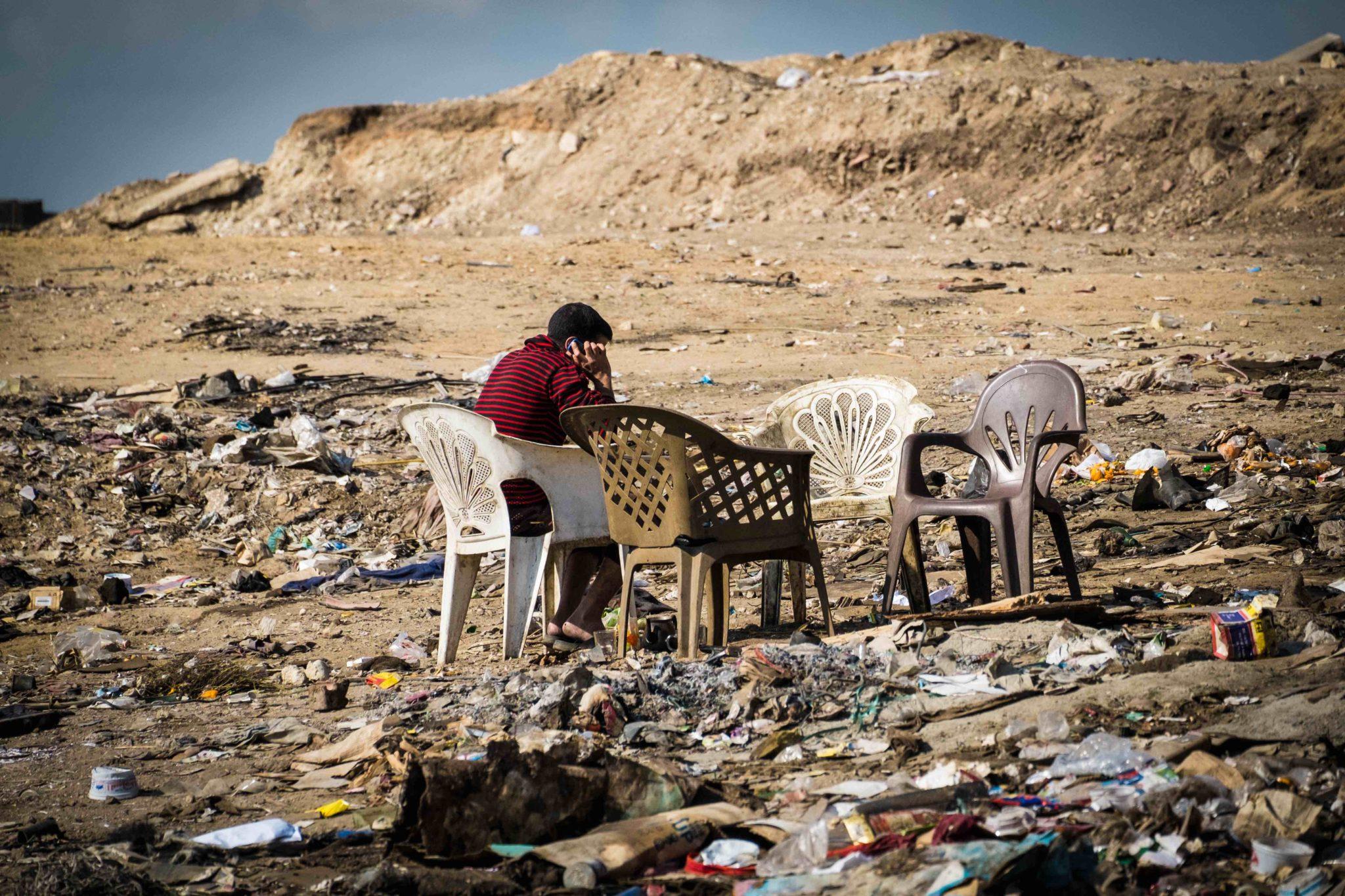 """Un uomo aspetta che gli venga servito un tè, queste 4 sedie in mezzo all'immondizia rappresentano uno dei """"caffè"""" di Muqattam. Foto di Angelo Calianno su licenza CC."""