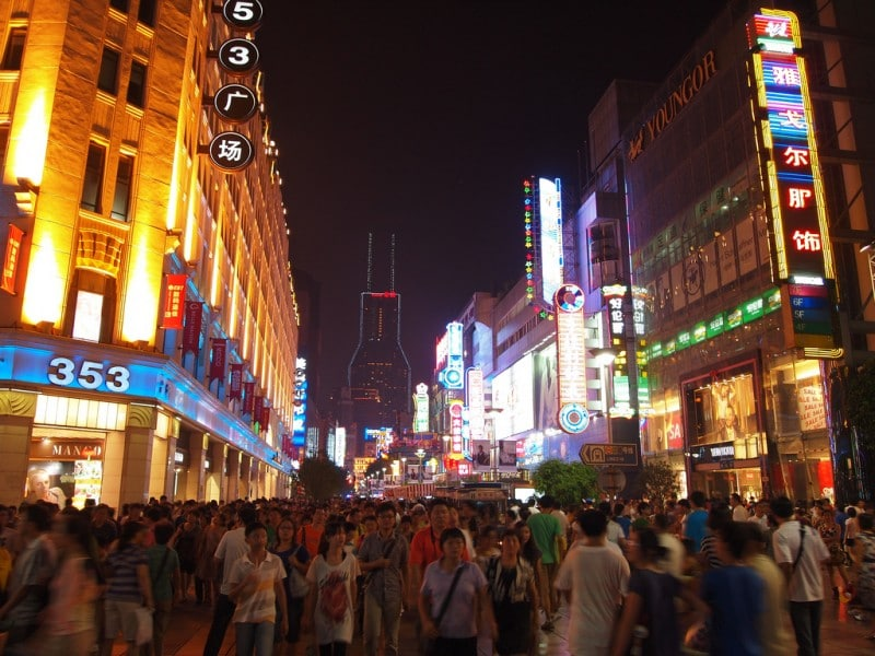 East Nanjing Road, Shanghai. The bustling pedestrian street is full of tourists, scam artists, families, prostitutes, salesmen, foreigners, beggars, thieves, and photographers. Photo by William via Flickr (CC BY-ND 2.0)