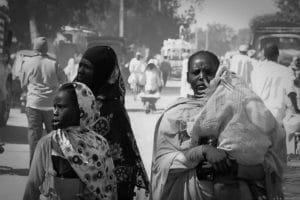 Bambini profughi nel villaggio di Kerma, in gruppo vicino ai banchetti di cibo per strada aspettando che qualcuno gli lasci qualcosa, qui mostrano un panino che gli è stato offerto. Foto di Angelo Calianno.