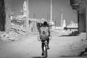 Un ragazzo in bicicletta percorre le strade di Suakin, secoli fa uno dei più importanti centri commerciali del mar Rosso, ora una città abbandonata e semi distrutta. Foto di Angelo Calianno.