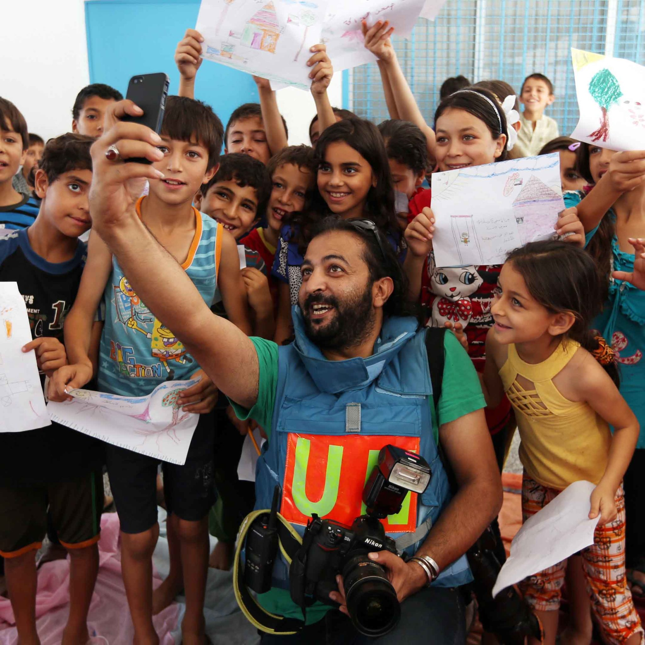 Il fotografo Shareef Sarhan in un selfie con i bambini del rifugio dell'URWA a Gaza, in Palestina.