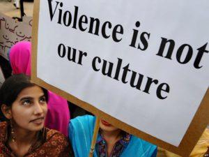 """Un'immagine di un'attivista pakistana che contiene un cartello: """"La violenza non è la nostra cultura"""""""