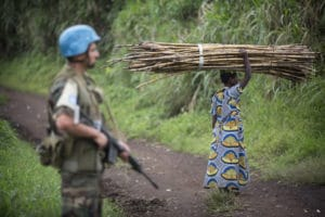 A peacekeeper on patrol as a resident gathers wood in the Beni region. Credit: UN Photo/Sylvain Liechti