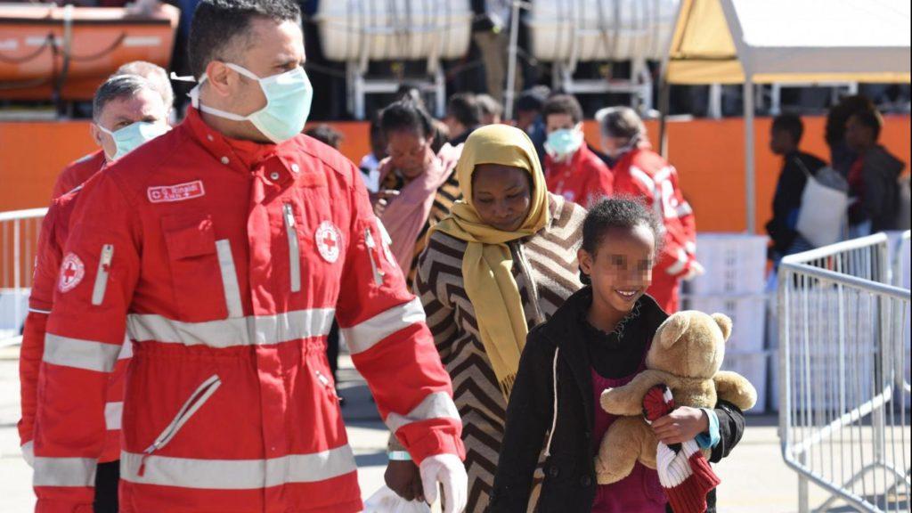 Lo sbarco di alcuni migranti da una delle navi della Guardia Costiera italiana