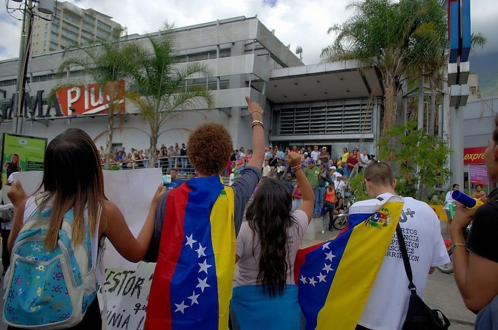 Dimostranti che invitano alla protesta la gente in fila per comprare beni di prima necessità. Fonte Flickr. Autore Carlos Díaz