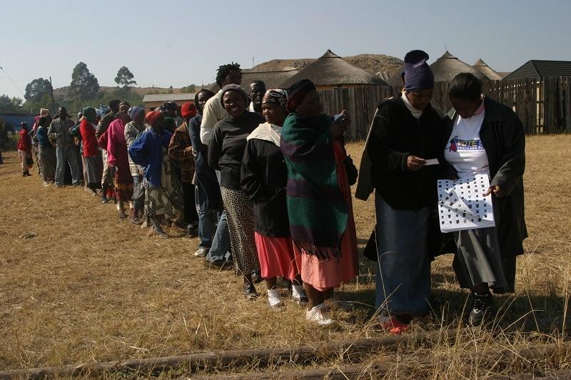 "Gli elettori in fila per esprimere il voto nel collegio elettorale di Motstane. Swaziland, 1 ottobre 2008. Immagine ripresa da <a href=""https://www.flickr.com/photos/ipsnews/8027196369/in/photolist-f4dTKu-7J8ehH-51Hci3-7K1eQf-XhnzbL-NQRoqo-7b9Hcw-7b5TqD-4pZn3k-7b9HX1-dektPp-5AXSon-8x2jNr-8NvvWy-VCmH86-F6FUQ3-GrdQyb"" target=""_blank"" rel=""noopener"">Flickr/News Agency</a> in licenza CC."