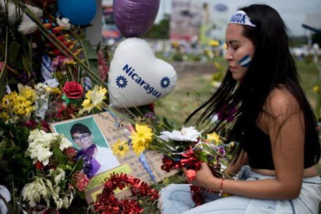 30 giugno 2018, Managua: una manifestante colloca dei fiori in onore alle vittime delle proteste contro il governo di Daniel Ortega. Foto: Carlos Herrera / dpa / PA Images. Tutti i diritti riservati.