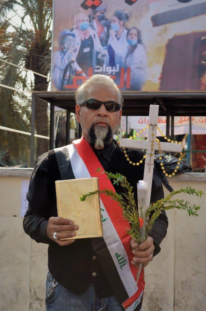 Un signore cristiano si presenta in piazza Tahrir, a Baghdad, ogni giorno. Con la sinistra porta la Croce, con un rosario e un ramo di mirto. Mentre nella destra porta il Corano