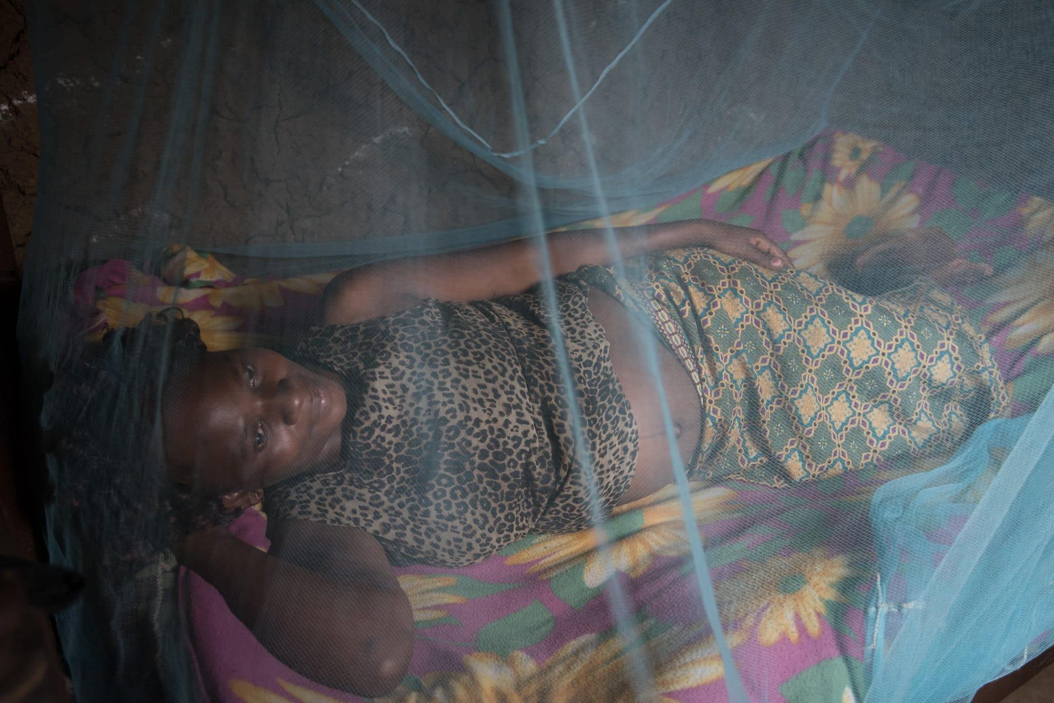 A Bungoma in Kenya, una donna incinta dorme sotto la sua zanzariera per proteggersi dalla malaria. Immagine ripresa da Flickr/Allan Gichigi MCSP in licenza CC.