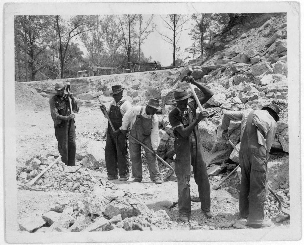 Carcerati spaccano pietre in un campo di prigionia o cantiere stradale | Libreria del Congresso su licenza libera.