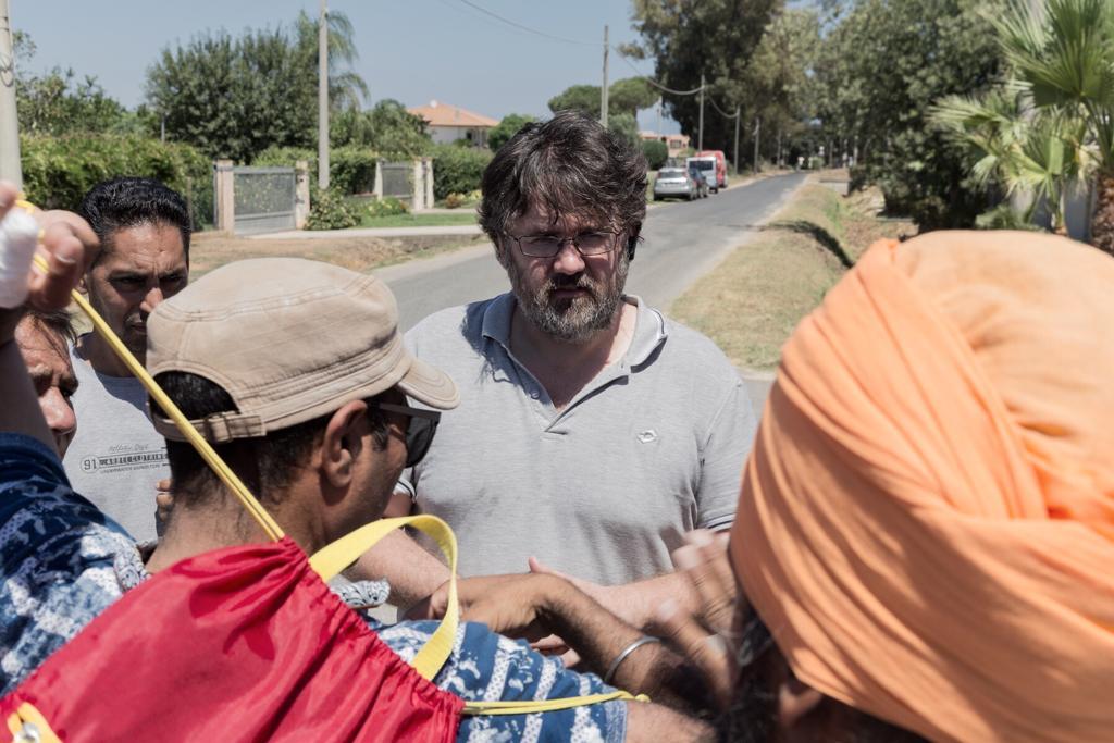 Marco Omizzolo con alcuni braccianti indiani nelle campagne pontine